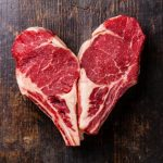 Heart shape Raw meat Ribeye steak entrecote on bone on wooden background